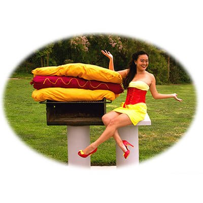 Competitive eater, Mary Bowers models her larger than life appetite with a hotdog big enough for the whole party