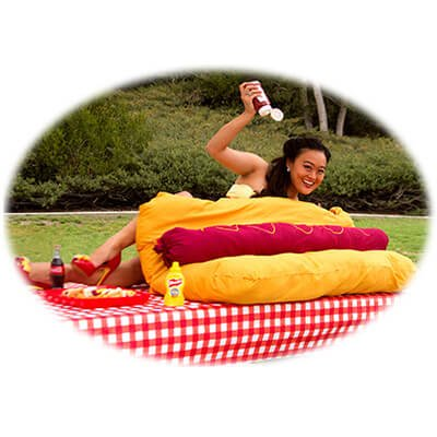Competitive eater, Mary Bowers relishes a summer picnic as she tops a giant hotdog with ketchup and mustard