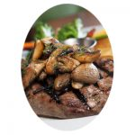 Bacon-Cured Skirt Steak recipe topped with mushrooms.